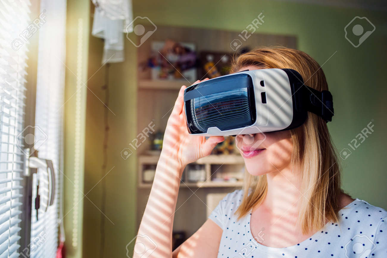 Virtual Reality Keuken : Blond woman wearing virtual reality goggles standing in a kitchen