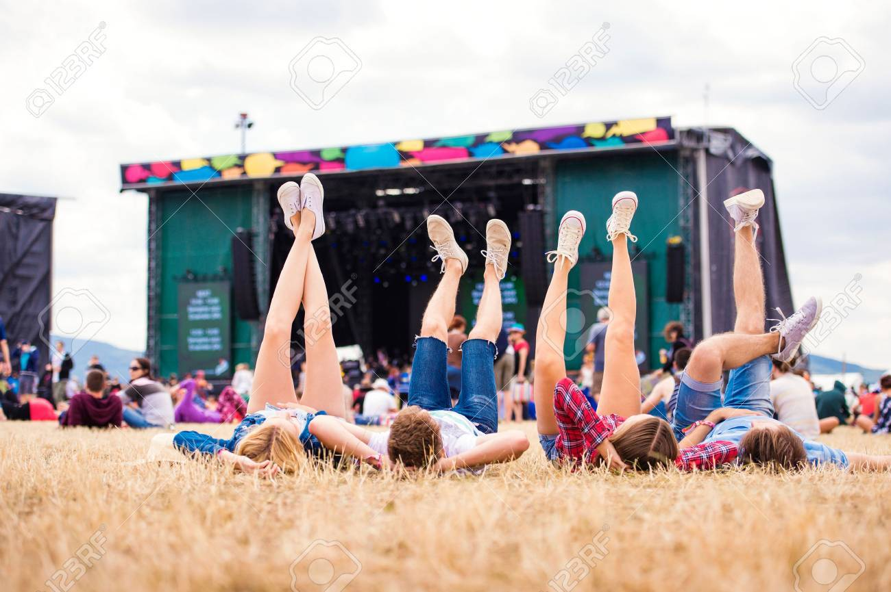 Legs of teenagers at summer music festival, lying on the grass in front of stage, rear view Banque d'images - 56785756