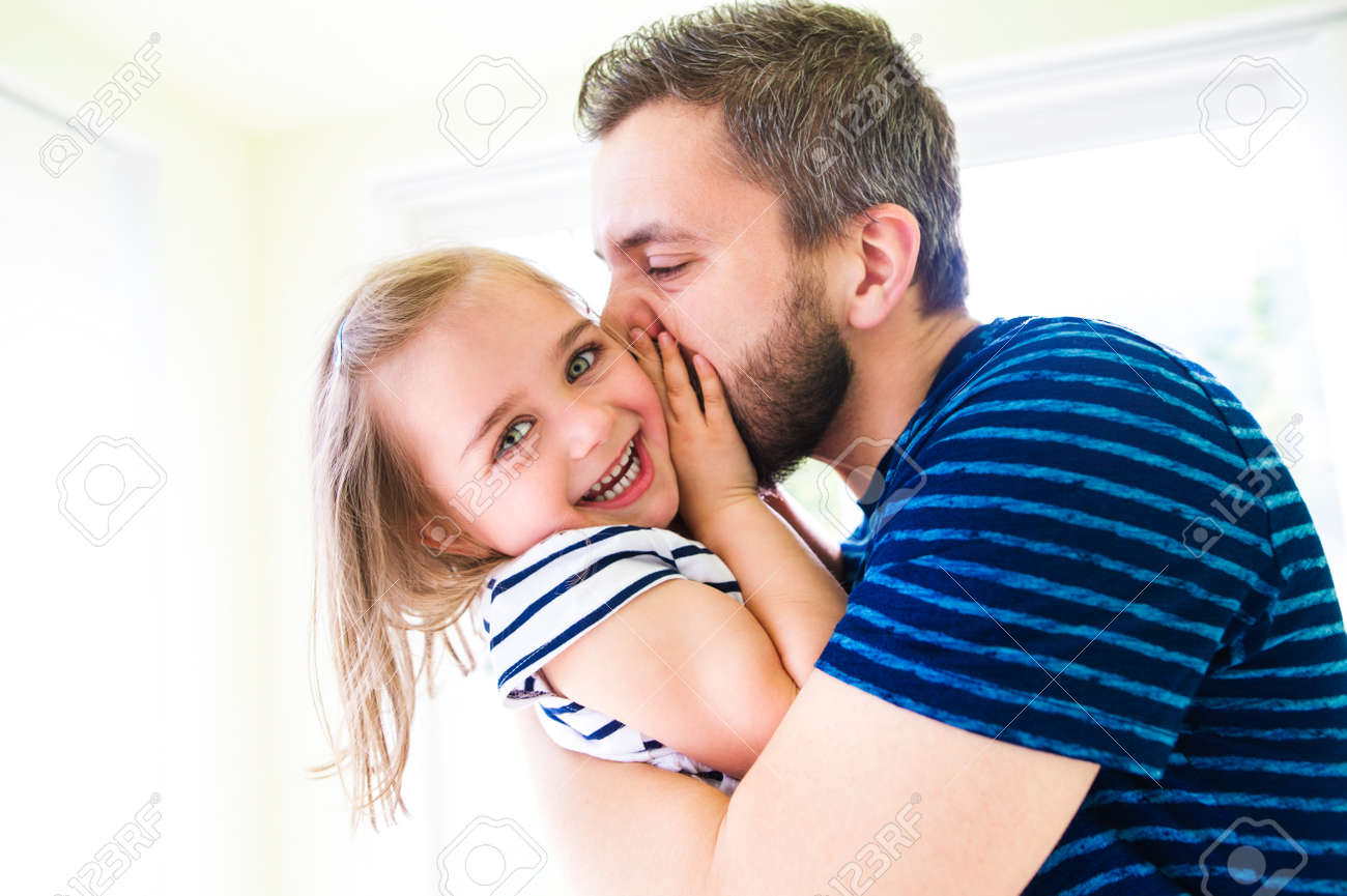 Close up of hipster father kissing his little daughter, sunny day Banque d'images - 56998185