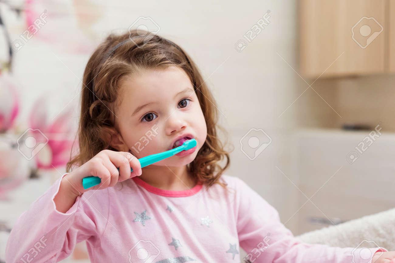 Nettes kleines Mädchen in den rosafarbenen Pyjamas im Badezimmer putzen  ihre Zähne