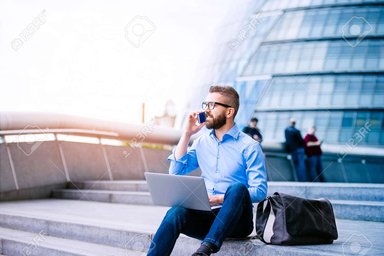 gestionnaire hipster Handsome assis sur les escaliers sur la journée ensoleillée, travaillant sur ordinateur portable, de parler sur un téléphone intelligent, Londres, City Hall Banque d'images - 57859749