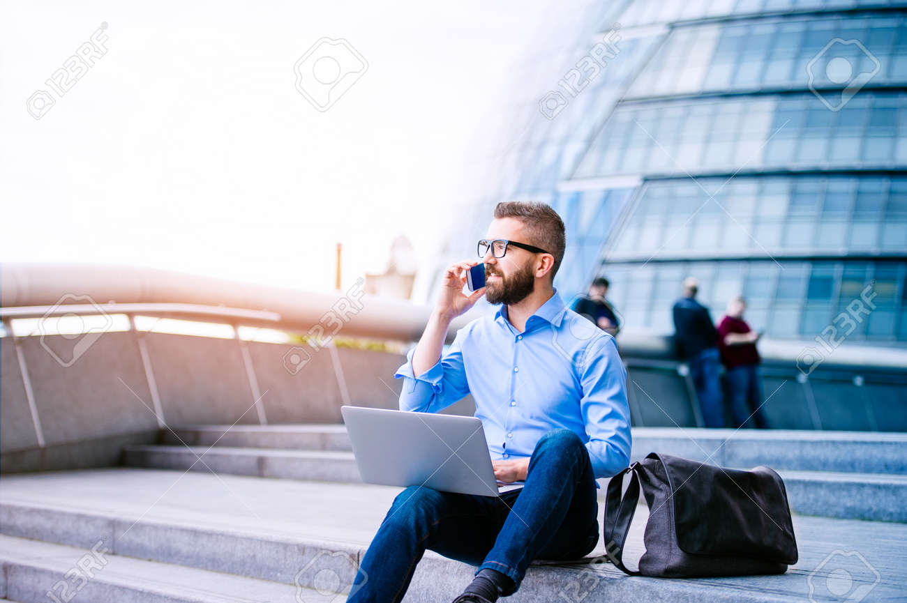 Handsome hipster manager sitting on stairs on sunny day, working on laptop, talking on a smart phone, London, City Hall - 57859749