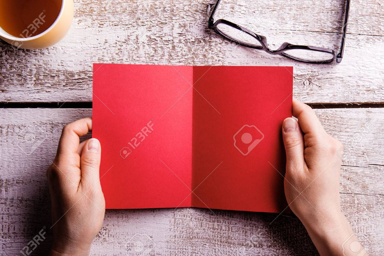 Mains de femme tenant méconnaissable vide rouge carte de voeux. Tasse de thé et des lunettes. Tourné en studio sur fond de bois. à plat, l'espace de copie. Banque d'images - 58471940