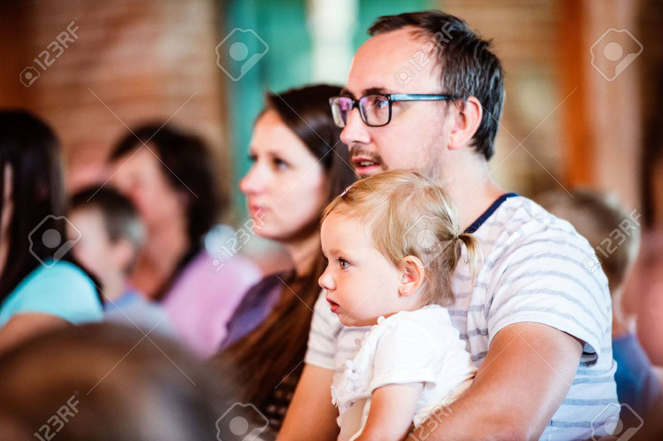 Young family with little daughter sitting outside in a crowd of people, watching show for children Banque d'images - 58576477