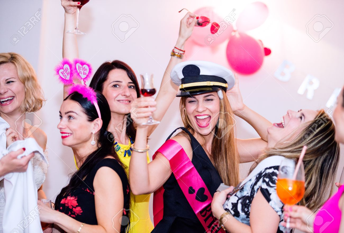 Cheerful bride and happy bridesmaids celebrating hen party with drinks. Women enjoying a bachelorette party dancing. Banque d'images - 58671415