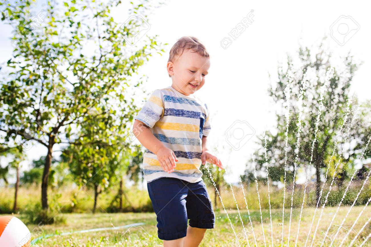 Kleiner Junge Am Regner Garten Grün Sonnigen Sommer Lizenzfreie