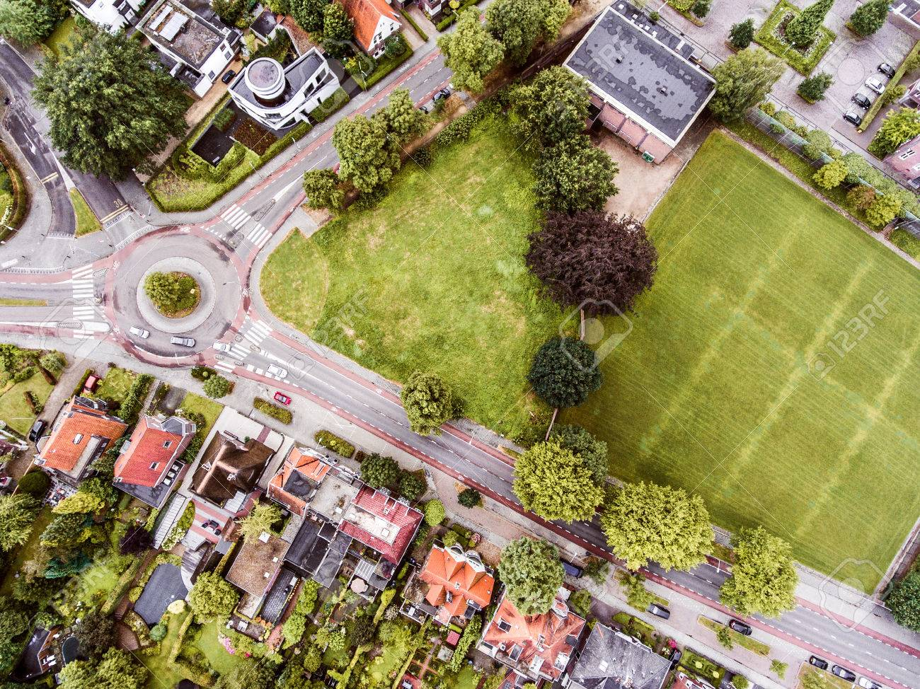 Aerial view of Dutch town, private houses, streets and roundabout, green park with trees - 61225635