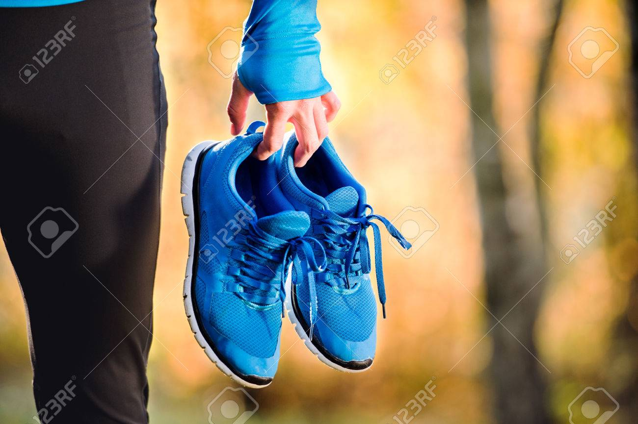 Unrecognizable runner in blue sweatshirt holding pair of sports shoes outside in colorful sunny autumn nature. - 61733476
