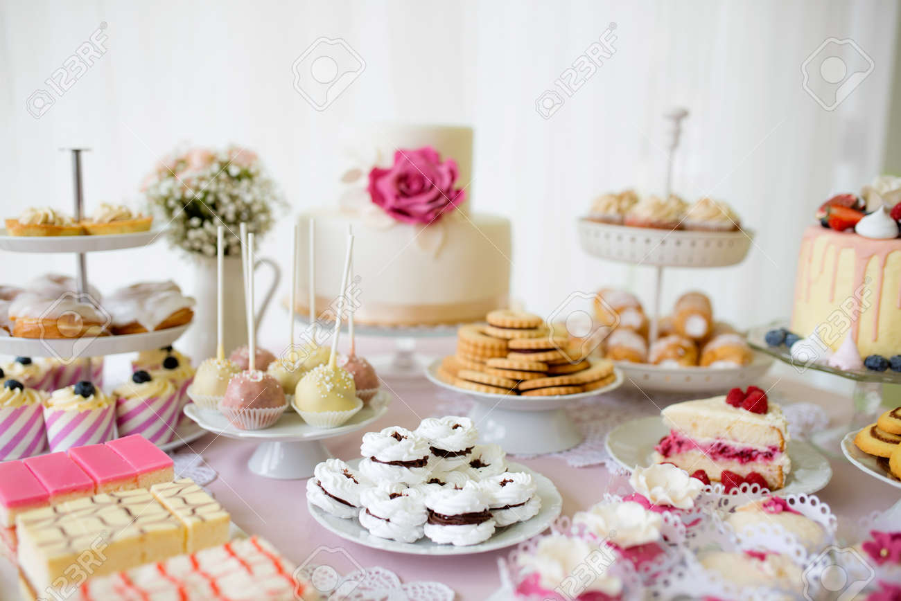 Table with loads of cakes, cupcakes, cookies and cakepops. Studio..