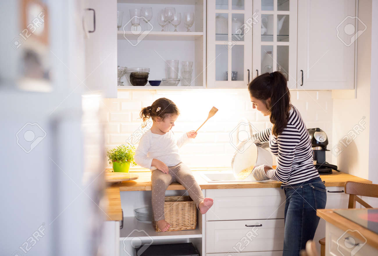Beautiful young mother with her cute little daughter in the kitchen, cooking pasta together - 65973133