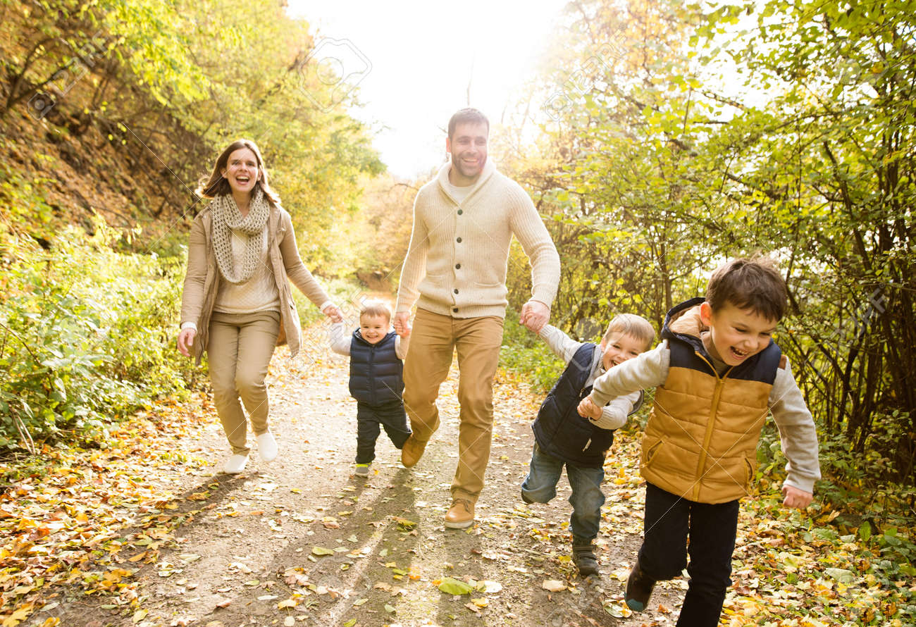 Beautiful young family on a walk in forest running mother and father with their
