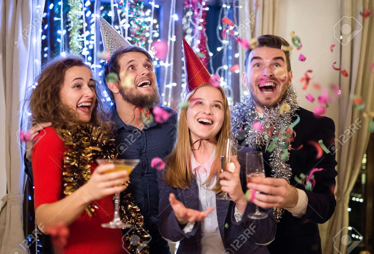 Groupe d'amis célébrant la fin de l'année, ayant partie le réveillon du Nouvel An, la tenue des verres de champagne. Banque d'images - 66947788