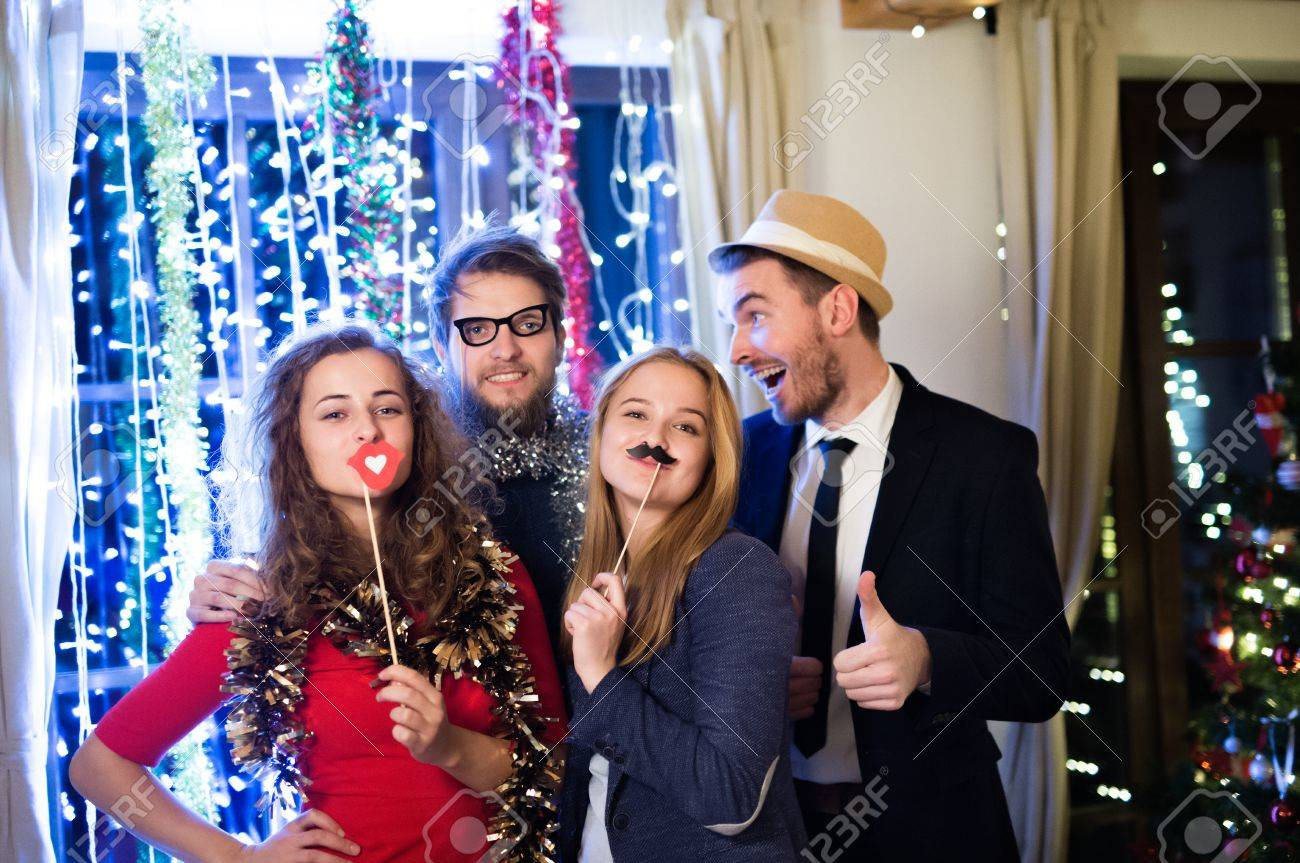 Beautiful hipster friends with photobooth props celebrating the end of the year, having party on New Years Eve, chain of lights behind them. Banque d'images - 67160956