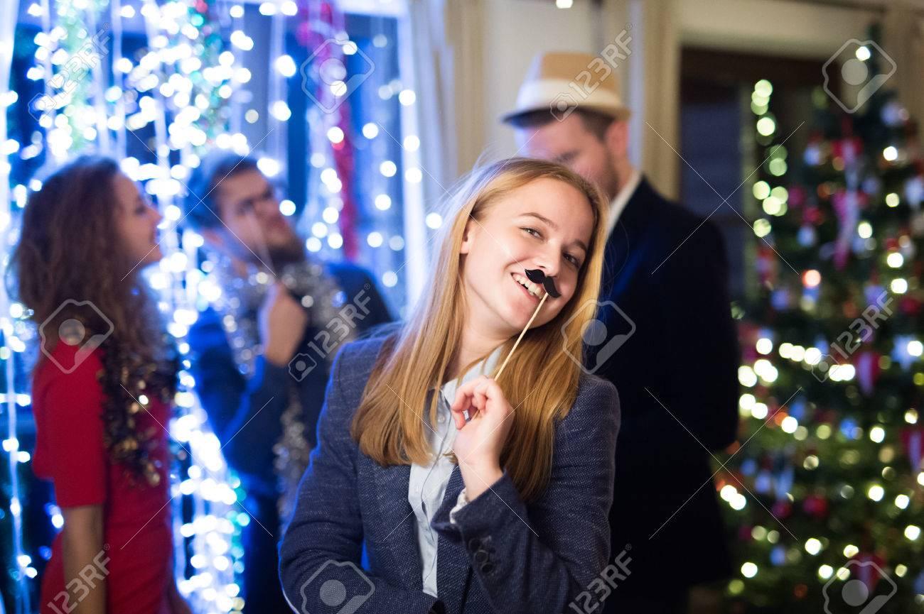 Belles amis hipster avec des accessoires de photomatons célébrant la fin de l'année, ayant partie le réveillon du Nouvel An, la chaîne de lumières derrière eux. Banque d'images - 67160992