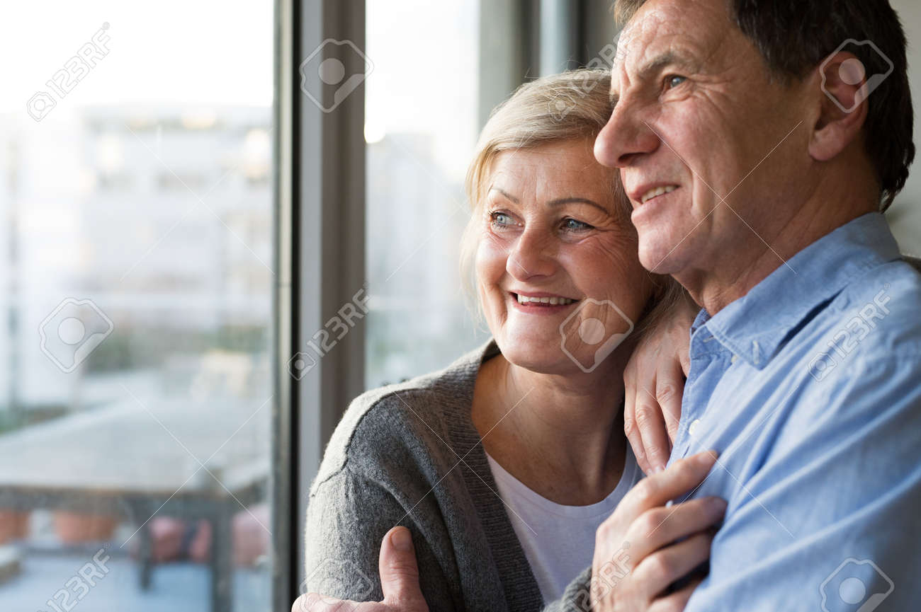Senior couple in living room standing at the window, hugging - 70377684
