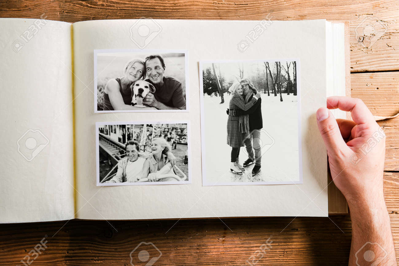 Fabuleux Hand Holding Photo Album With Pictures Of Senior Couple. Studio  RG73