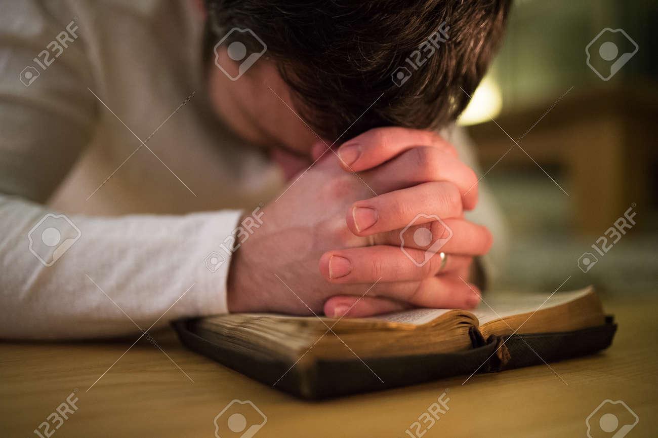 Unrecognizable man praying, kneeling on the floor, hands on Bibl Banque d'images - 71185378
