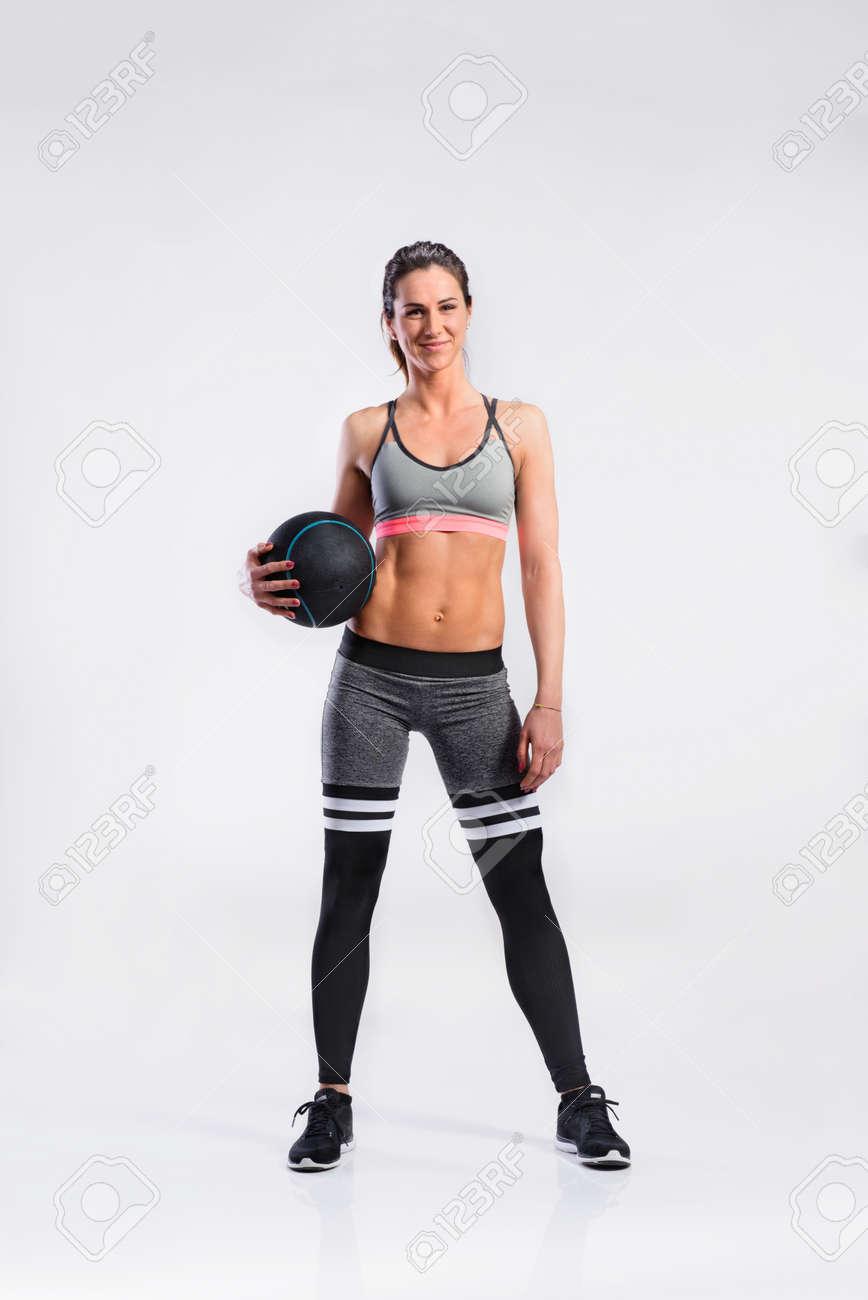 magasiner pour l'original procédés de teinture minutieux style de mode Femme de fitness en tenue de sport tenant ballon de médecine, studio s