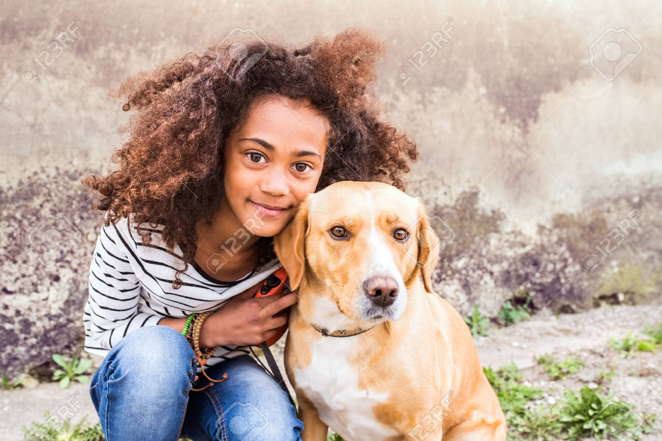 African american girl with her dog against concrete wall. - 83869842