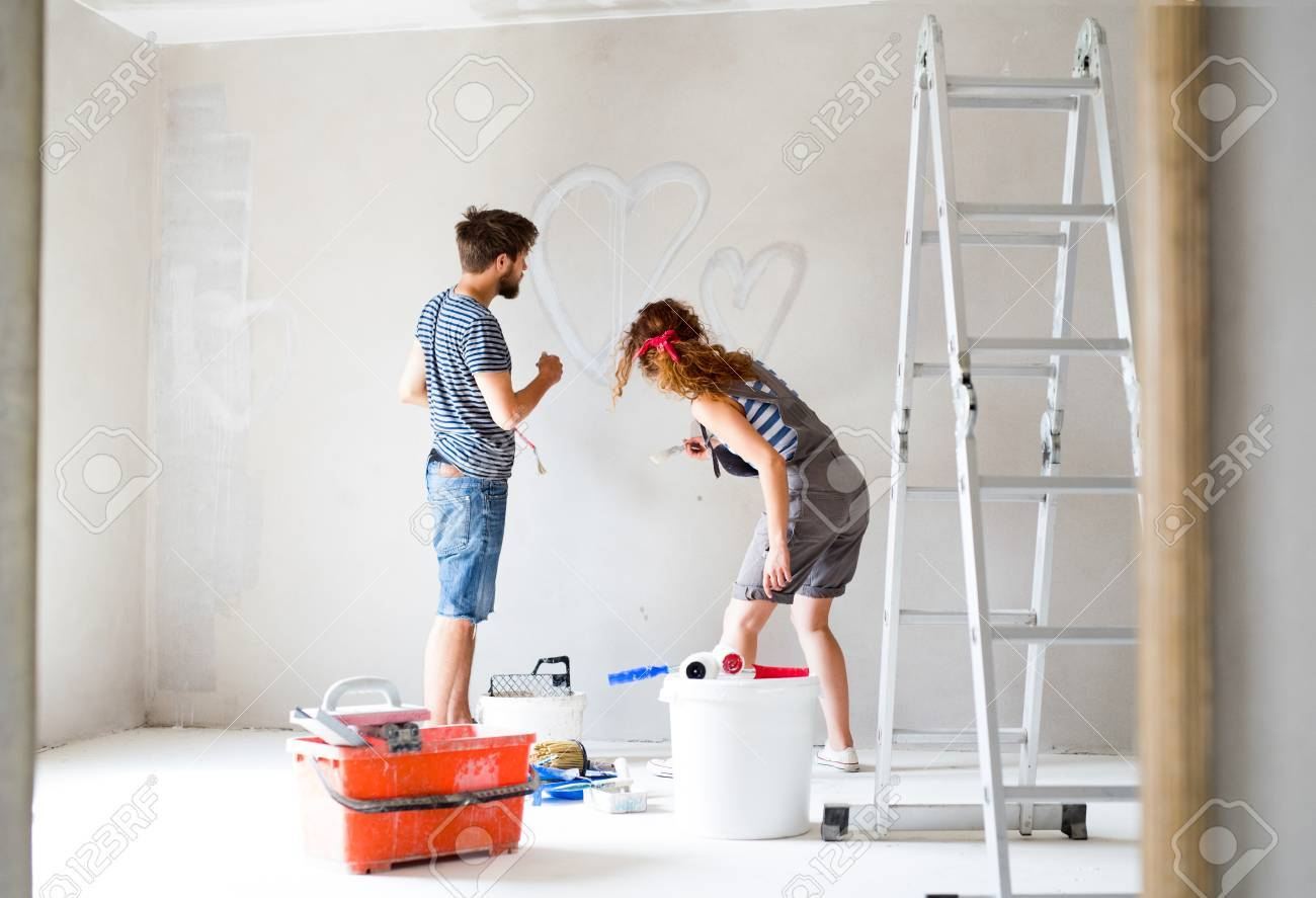 Young Couple Painting Walls In Their New House