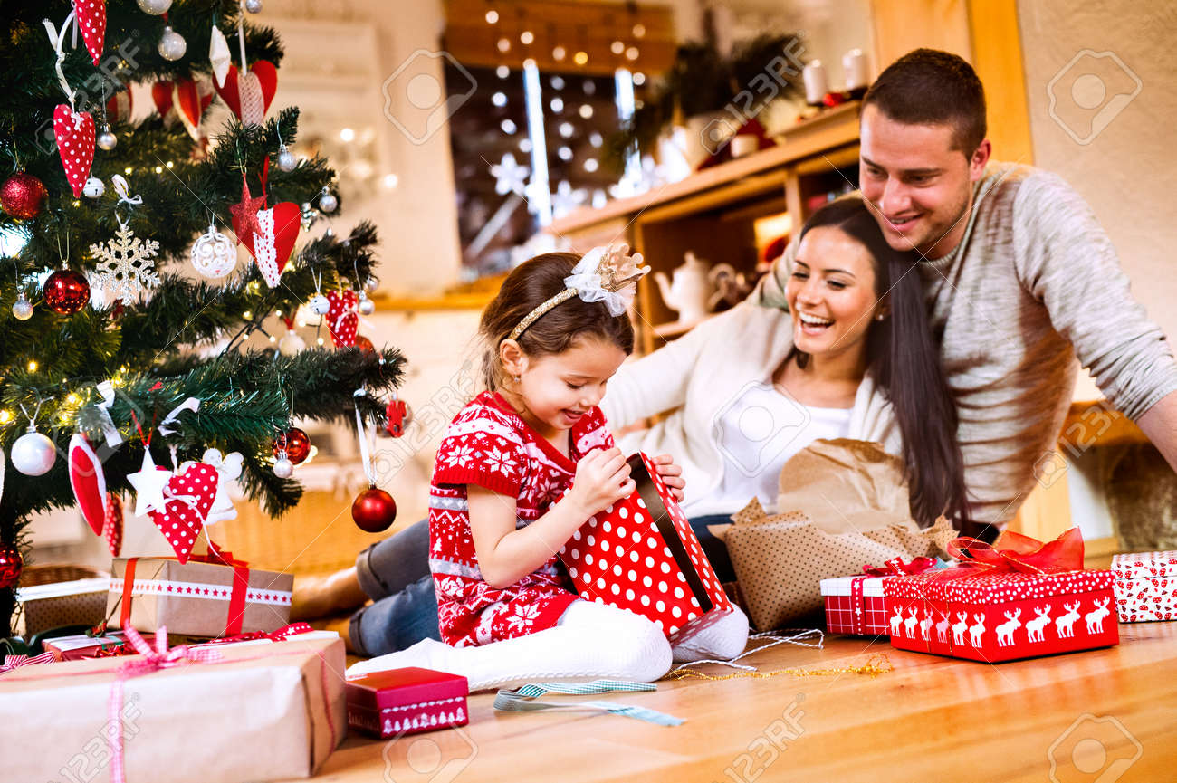Young family with daughter at Christmas tree at home. - 87265310