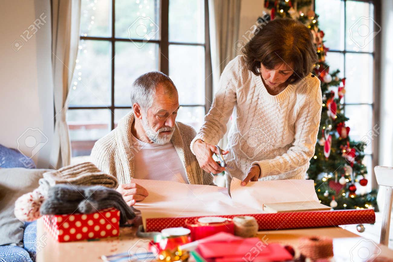 Ltere Paare In Den Strickjacken, Die Zusammen Weihnachtsgeschenke ...