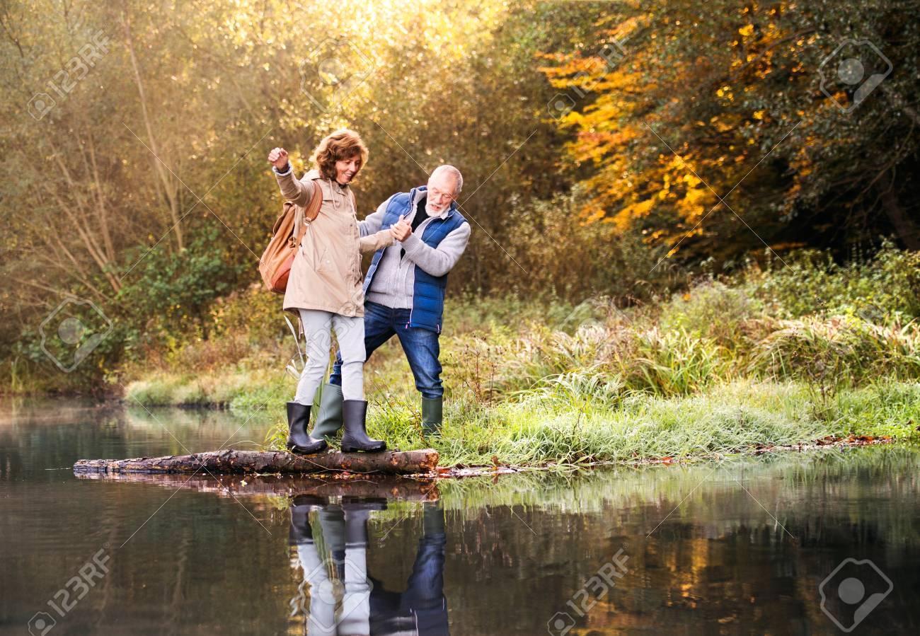 Senior couple on a walk in autumn nature. - 89199360