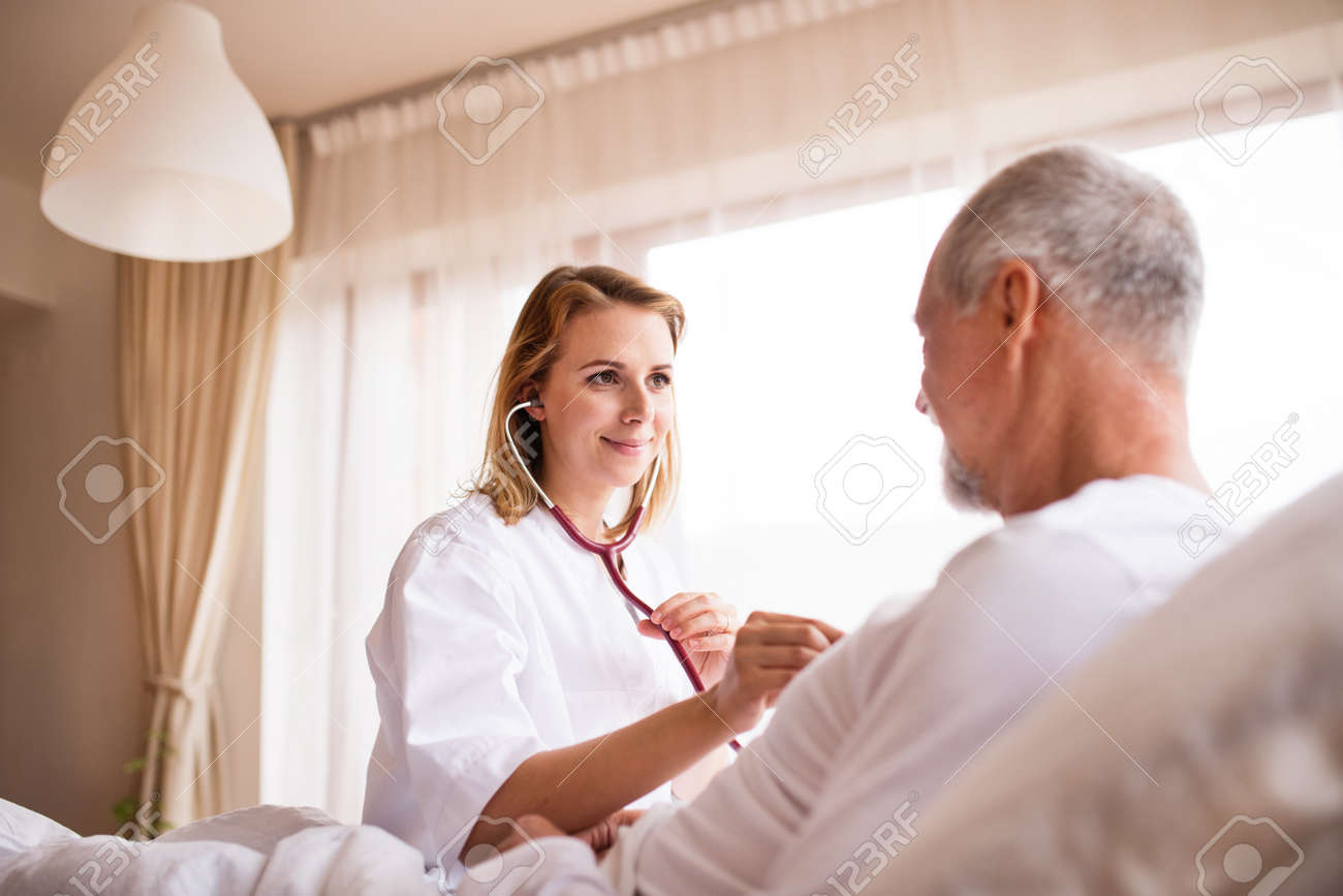 Health visitor and a senior man during home visit. - 90758313
