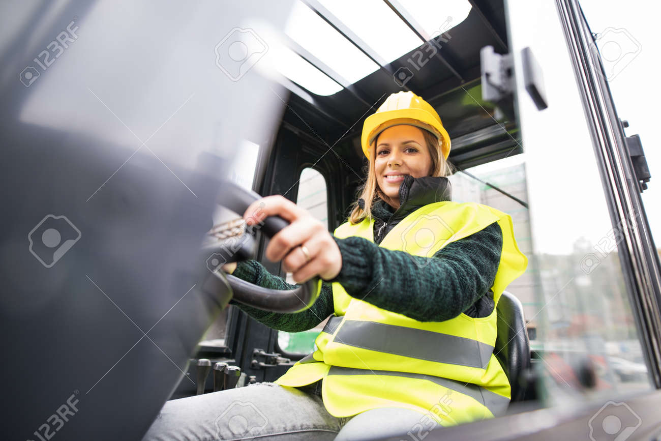 Woman forklift truck driver in an industrial area. - 91413809