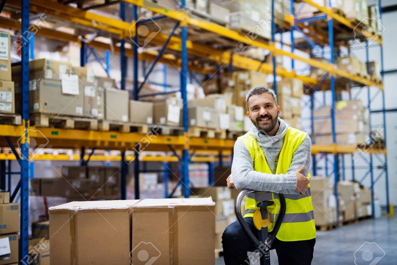 Male warehouse worker standing by a pallet truck. - 91531522