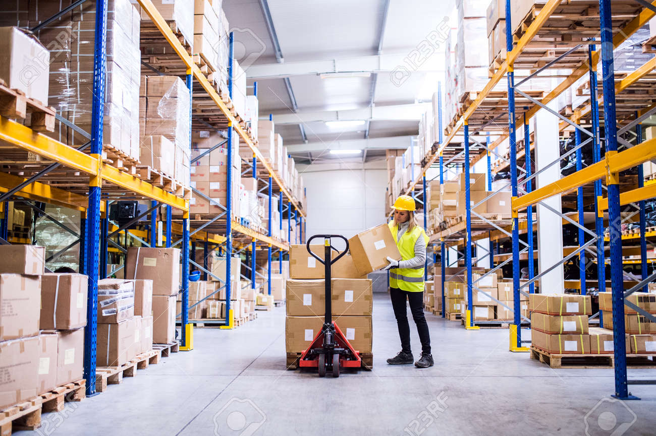Female warehouse worker loading or unloading boxes. - 92049923