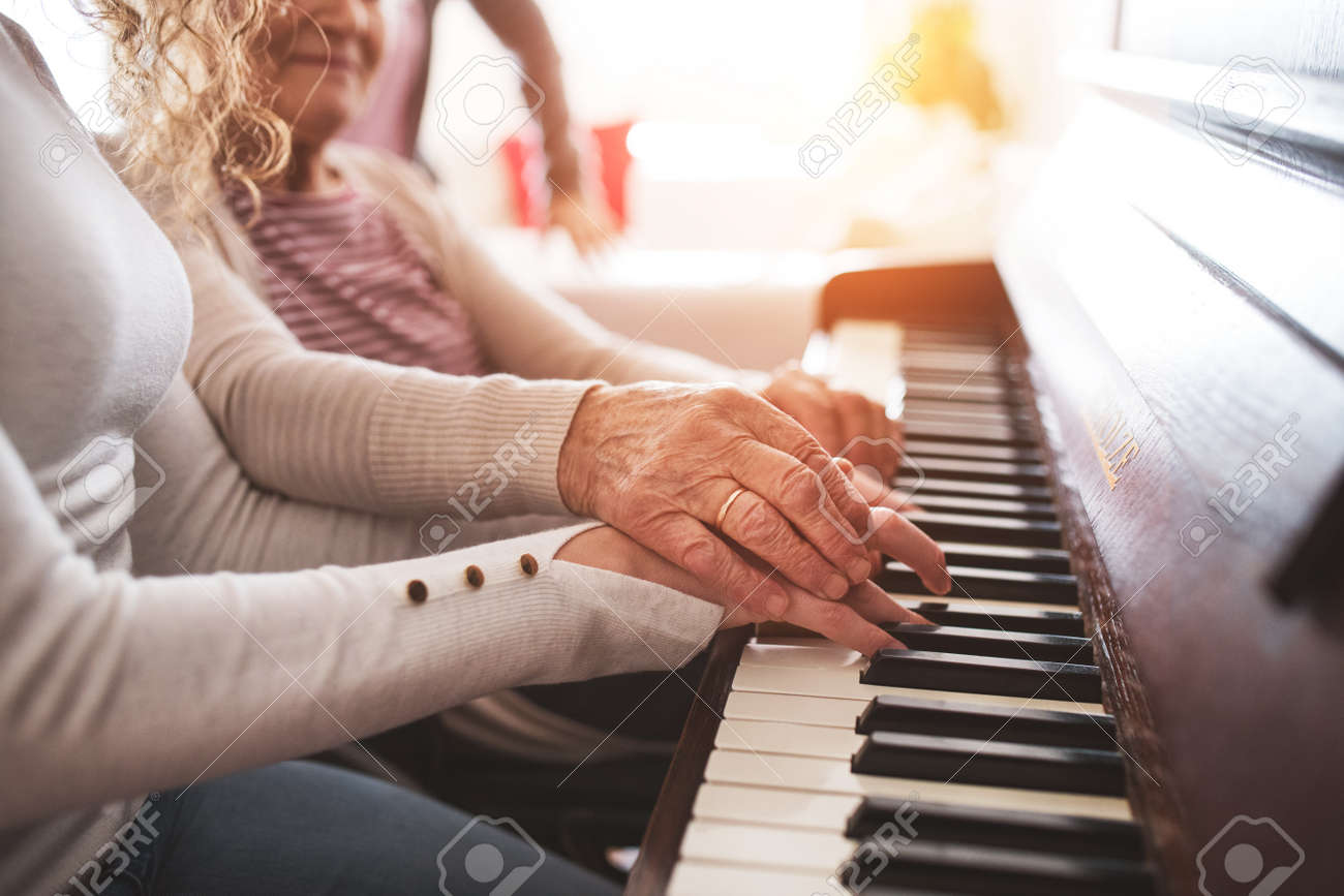 A girl with grandmother playing the piano. - 95243027