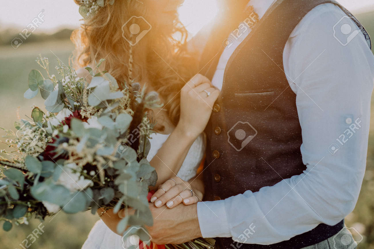 Beautiful bride and groom at sunset in green nature. - 95844201