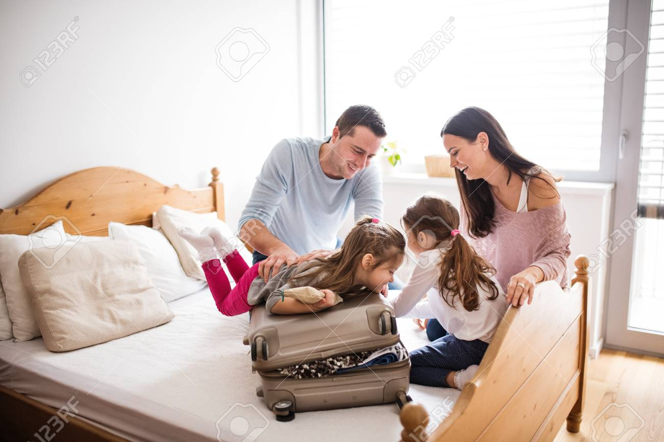 Young family with two children packing for holiday. - 101089792