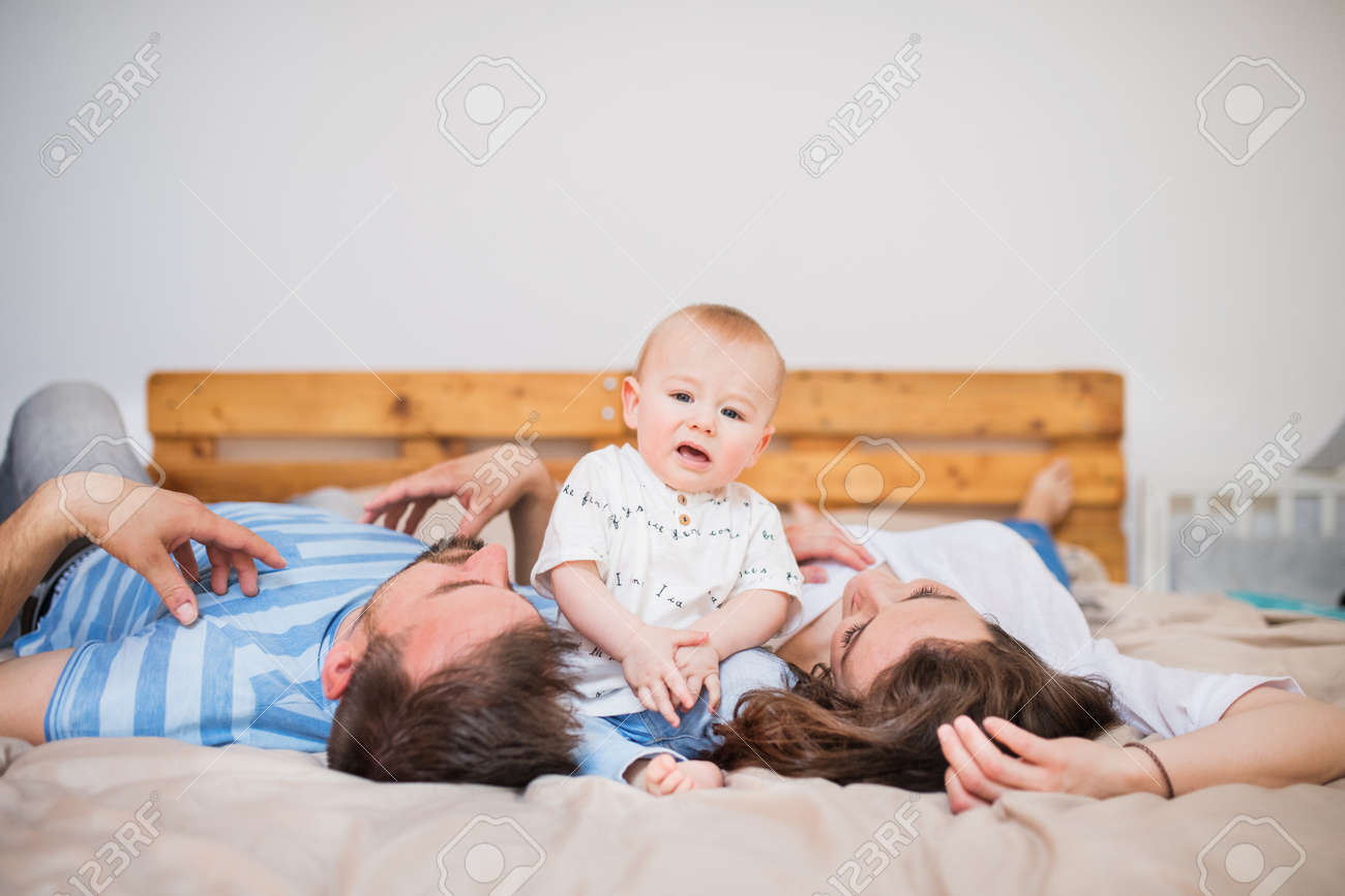 Stock photo young family with a baby boy at home lying on bed