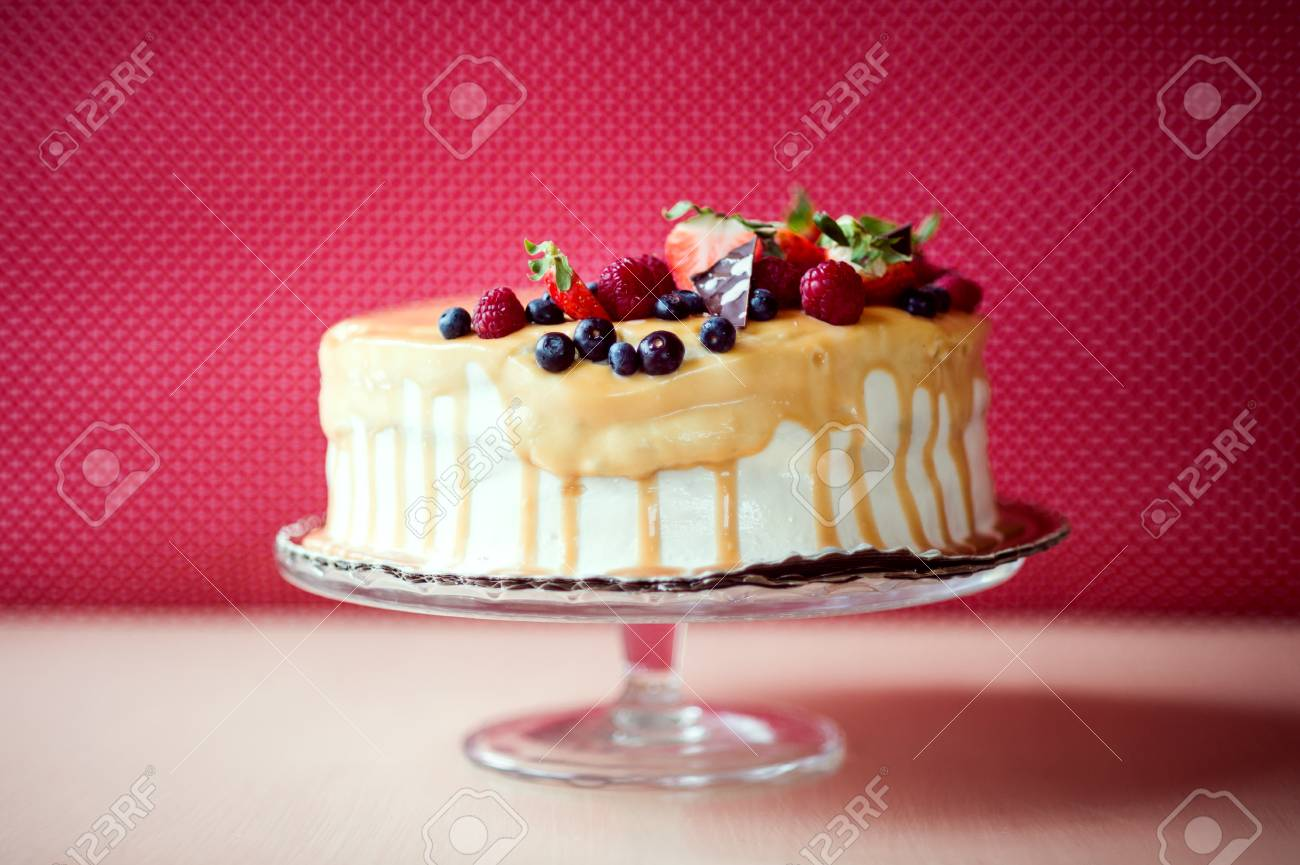 A Birthday Cake On A Glass Stand On The Table Fruit On Top Stock