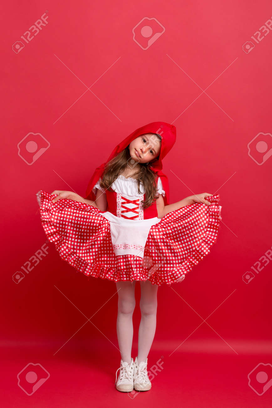 A Small Girl In Little Red Riding Hood Costume In Studio On A