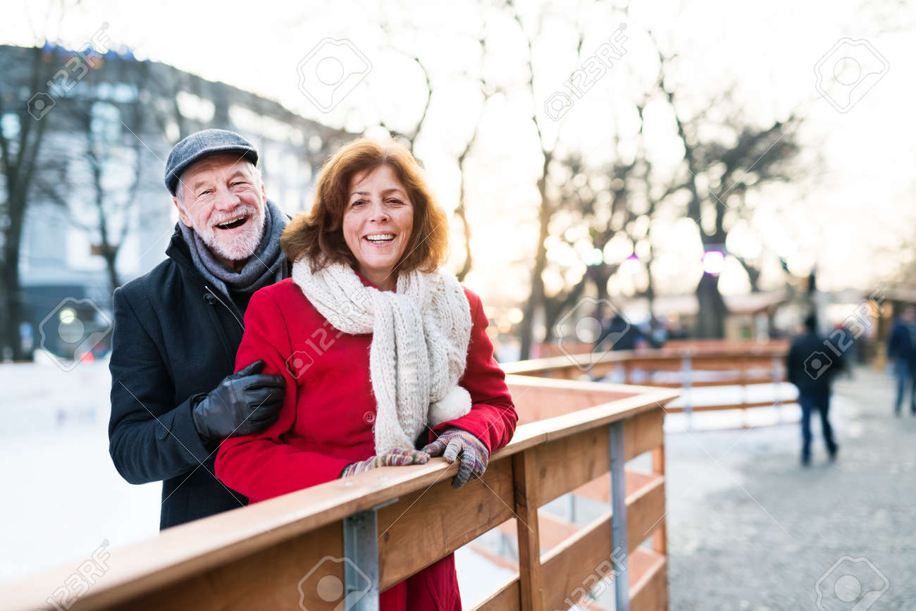Senior couple on a walk in a city in winter. - 108155892
