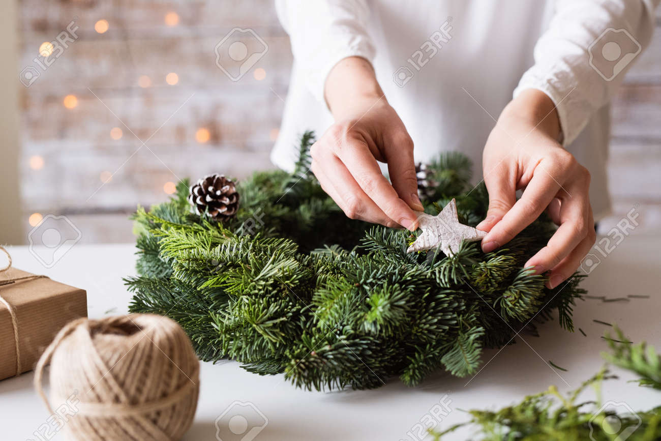 Hands of unrecognizable woman decorating christmas wreath. - 108595444