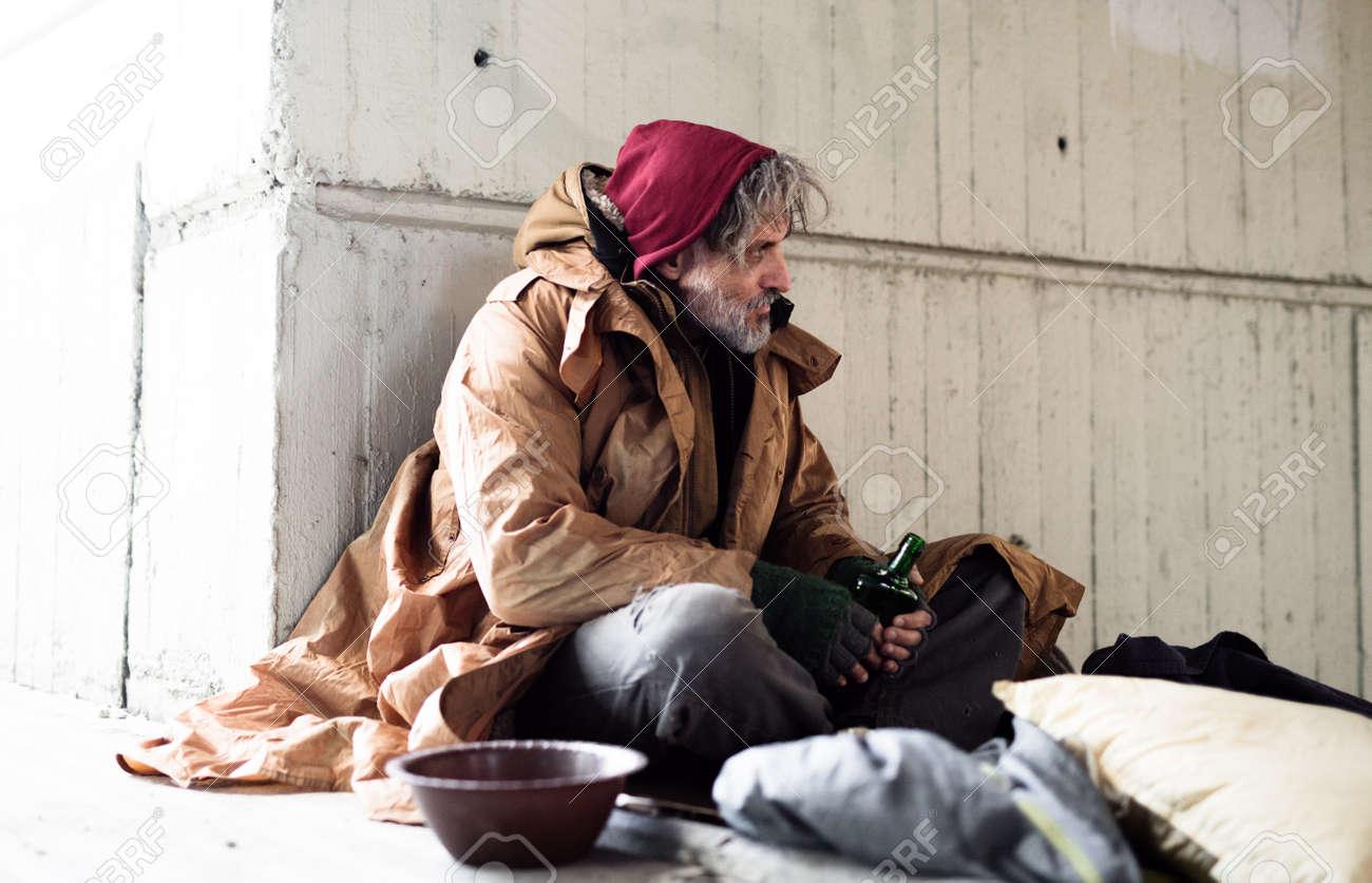 Homeless beggar man sitting outdoors in city asking for money donation. - 112649527