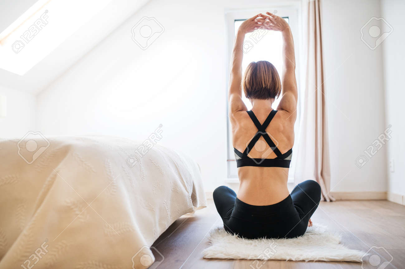 A rear view of young woman doing exercise indoors in a bedroom. Copy space. - 113294364