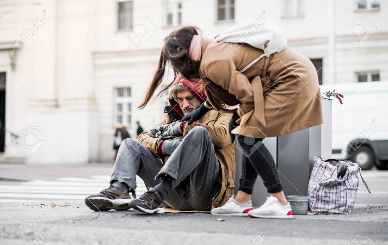 Young woman giving money to homeless beggar man sitting in city. - 115295263