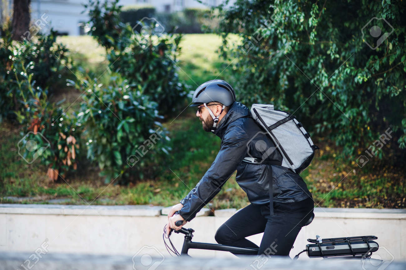 Male bicycle courier delivering packages in city. Copy space. - 115657048