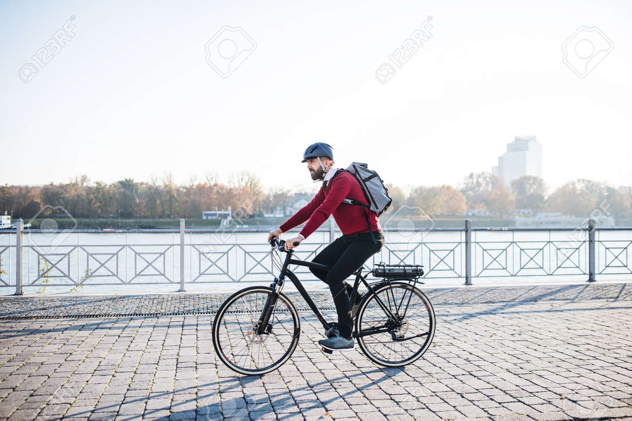 Hipster businessman commuter with electric bicycle traveling to work in city. - 115657523