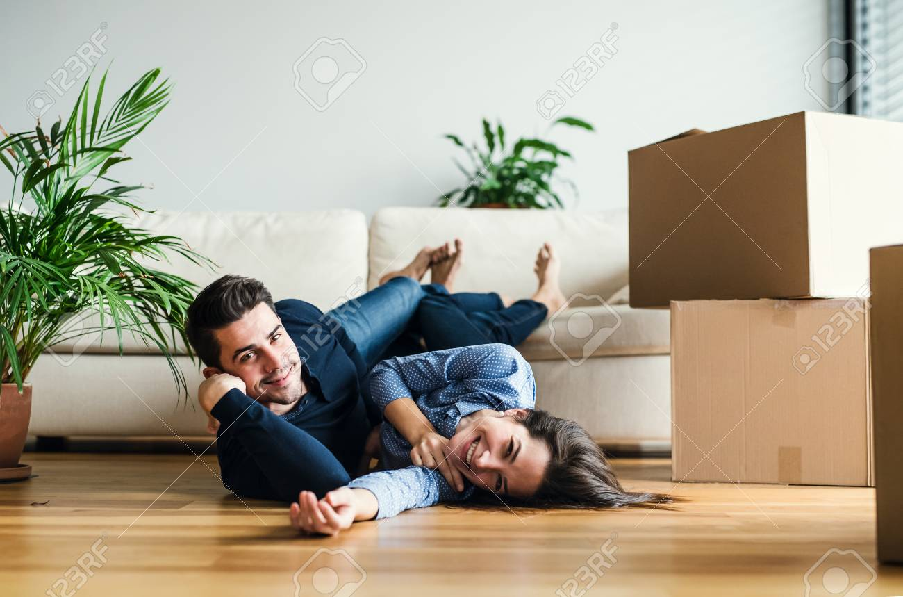 A young couple with cardboard boxes moving in a new home. - 115903038