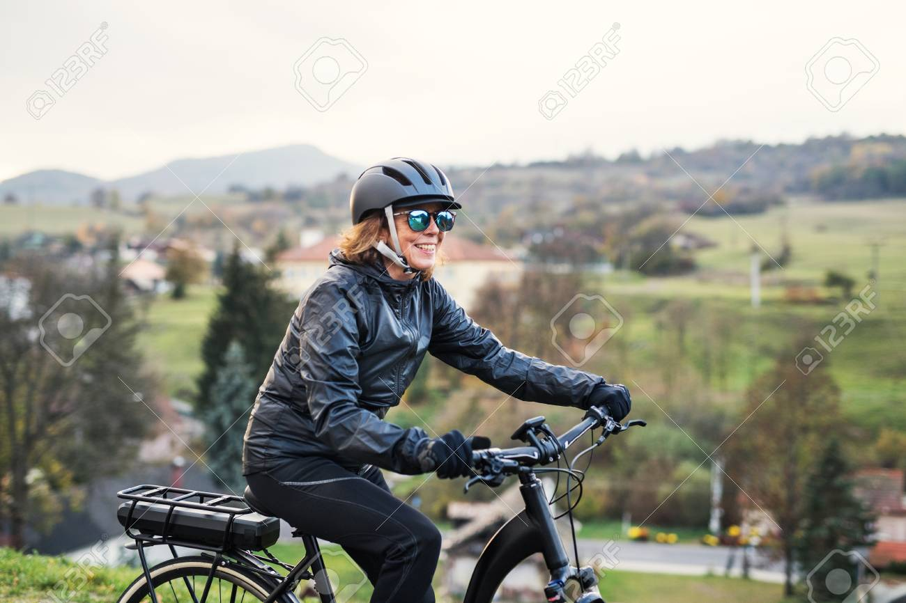 A side view of senior woman with electrobike cycling outdoors in countryside. - 116367110