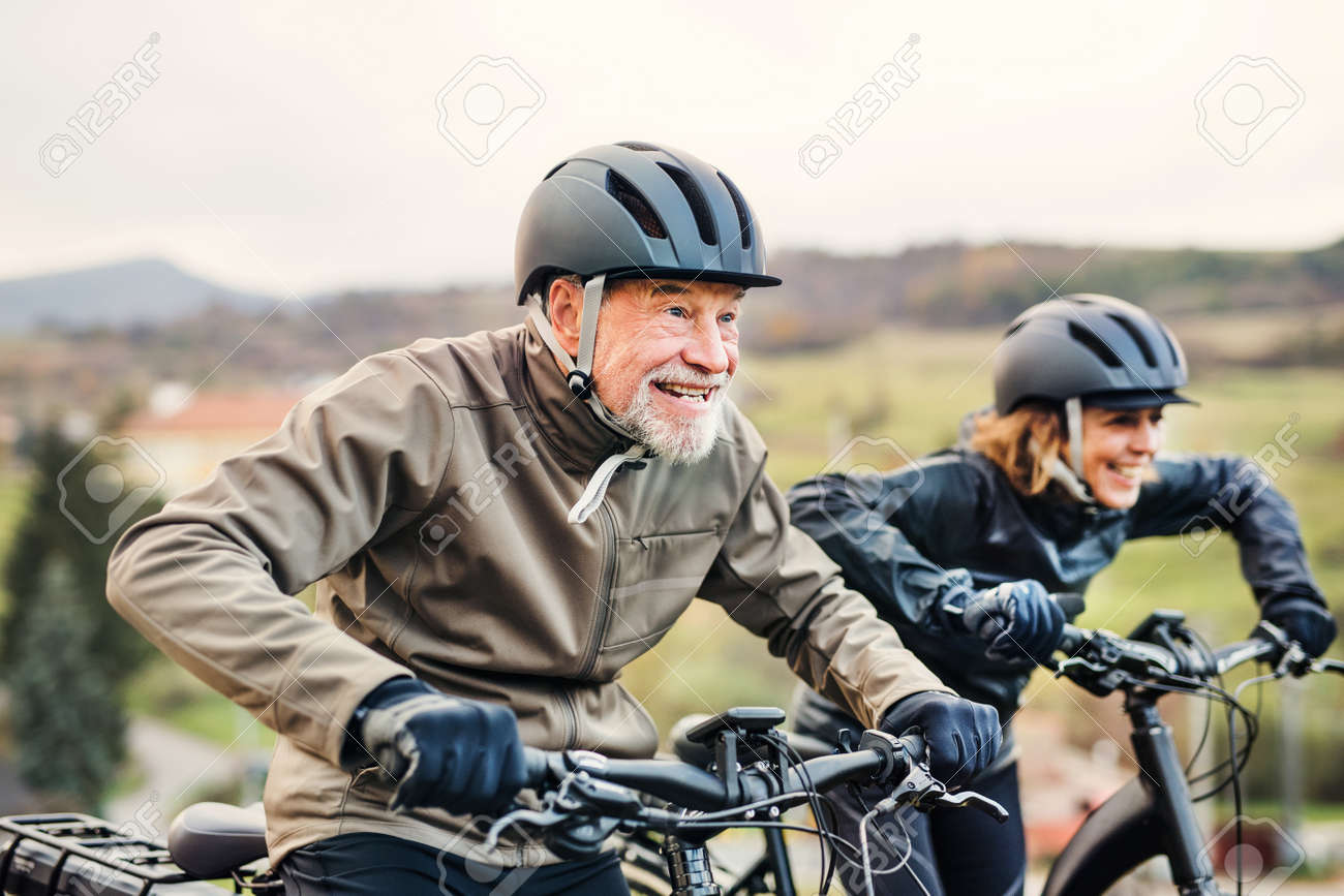 Active senior couple with electrobikes cycling outdoors on a road in nature. - 116381389