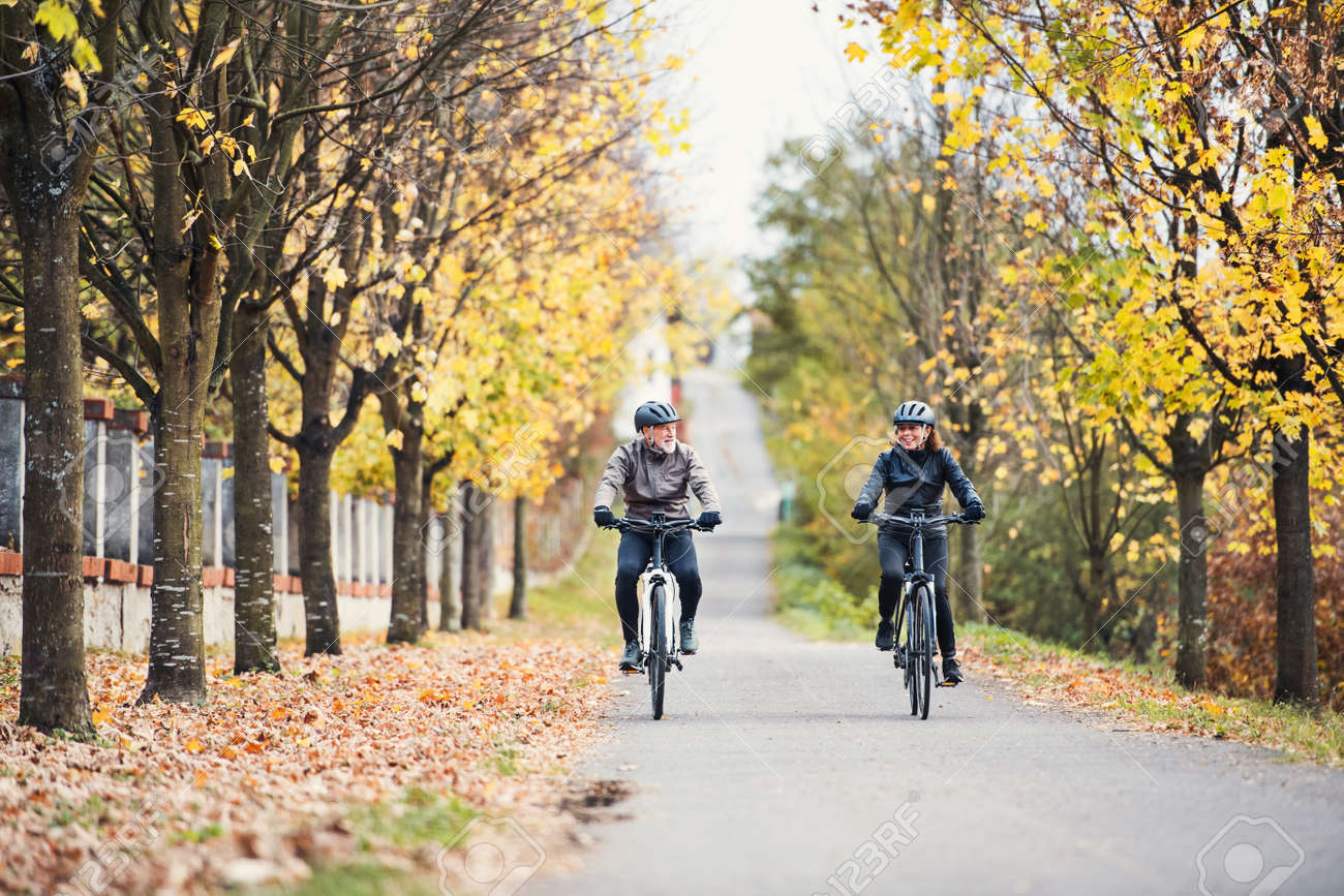 A senior couple with electrobikes cycling outdoors on a road. - 116646822