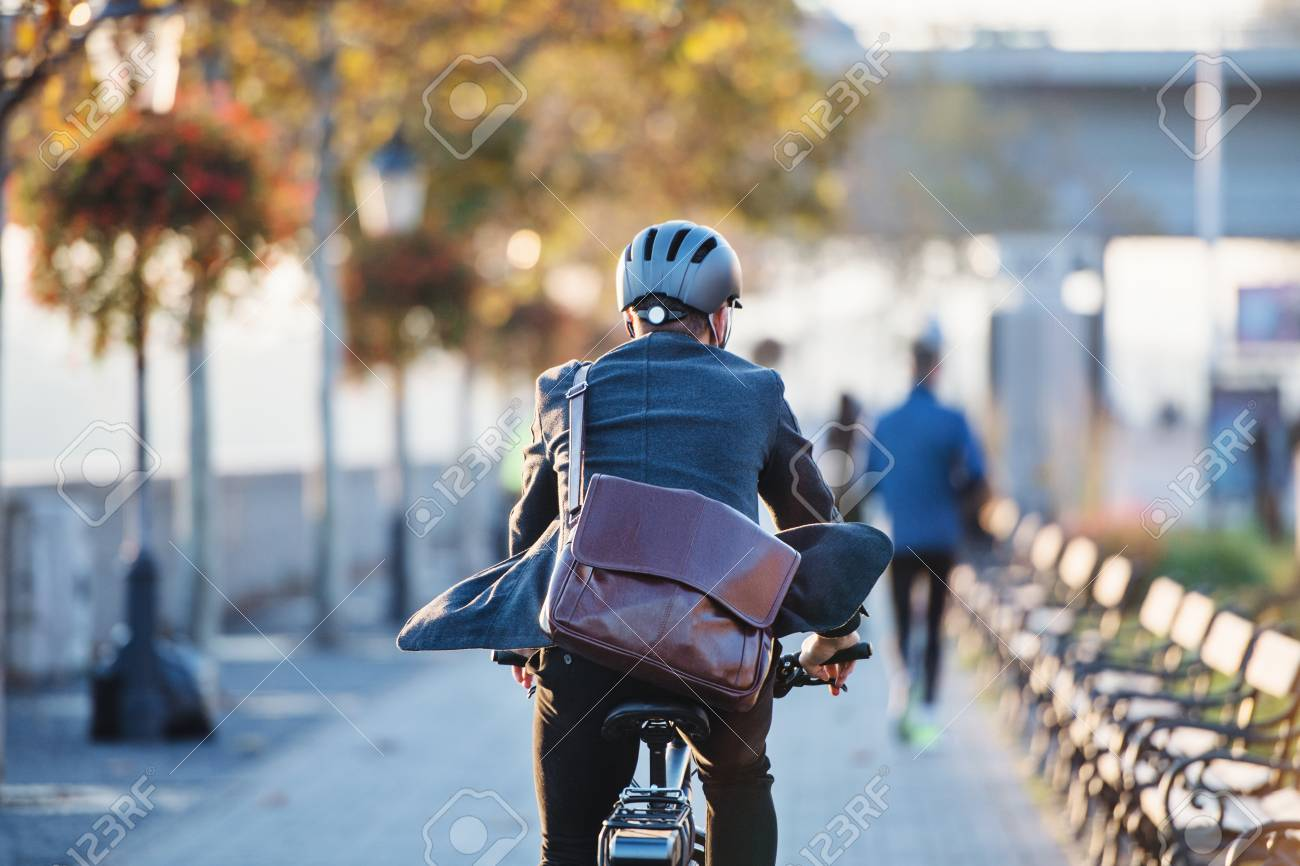 A rear view of businessman commuter with electric bicycle traveling to work in city. - 117699054
