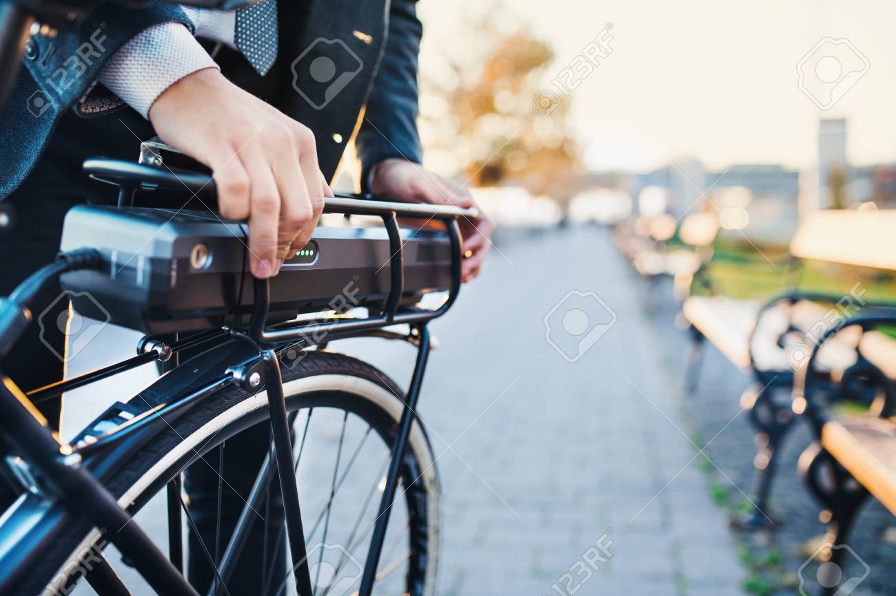 A midsection of businessman commuter setting up electric bicycle in city. - 118075638